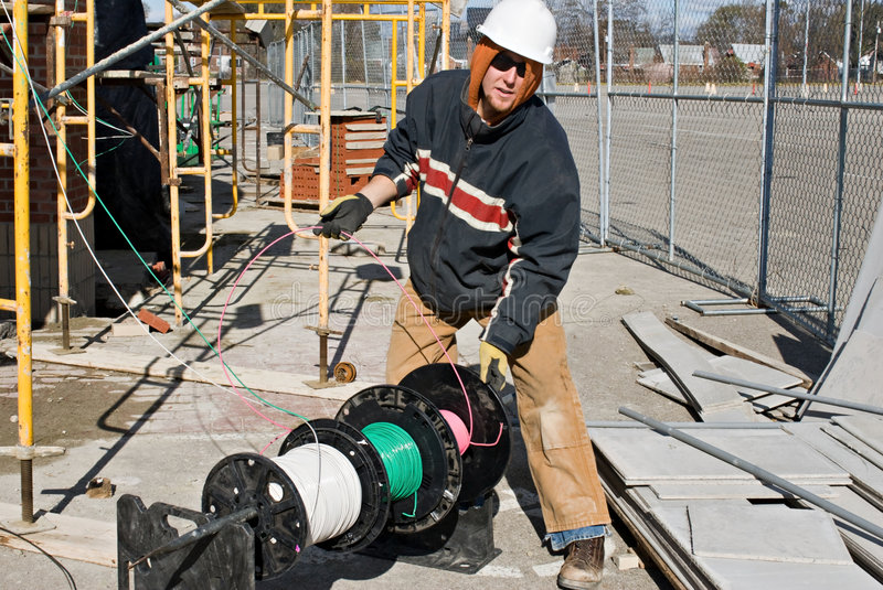 Electrician Unwinding Wire. Construction electrician unwinding electrical cables from spools stock photography