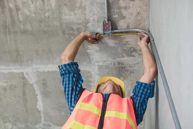 Electrician use measuring tape to measure electrical pipe in renovation building stock photography