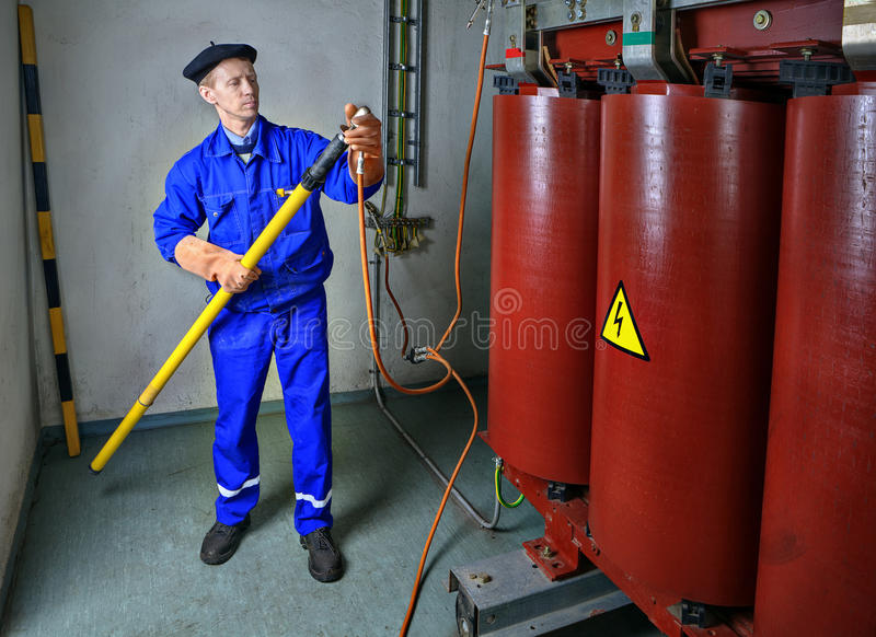 Electrician uses an insulating stick Earthing transformer. royalty free stock image