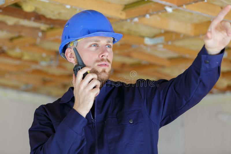 Electrician uses walkie talkie to communicate with team stock photo