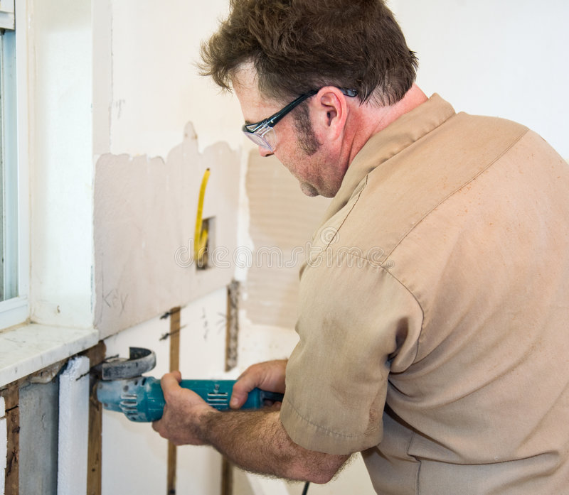 Electrician Using Grinder. Electrician using a grinder to cut through insulation in a wall. Authentic and accurate content depiction in accordance with industry stock image