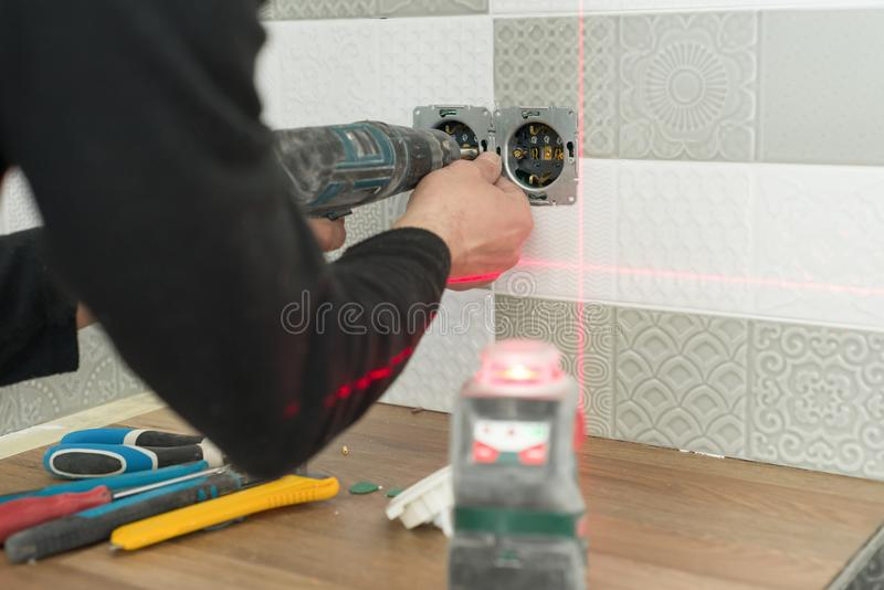 Electrician using infrared laser level to install electrical outlets. Renovation and construction in kitchen royalty free stock photography