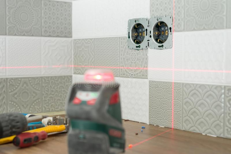 Electrician using infrared laser level to install electrical outlets. Renovation and construction in kitchen stock photo