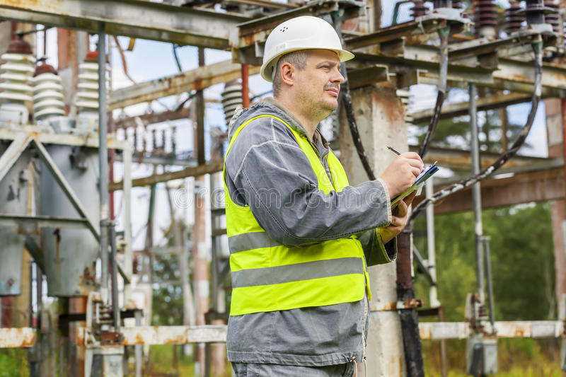 Electrician using tablet PC in electrical substation royalty free stock image