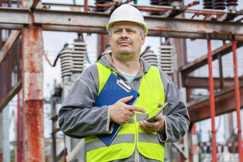 Electrician using tablet PC and take substation technical inspection royalty free stock image
