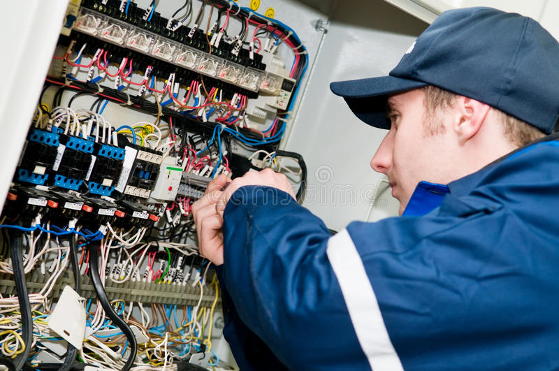 Electrician at voltage adjusting. One electrician working on a industrial panel mounting, assembling, adjusting new voltage wiring royalty free stock image