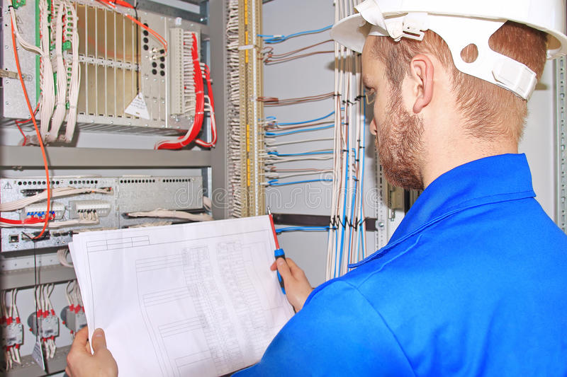 Electrician in white helmet is looking at electrical diagram in control cabinet of industrial equipment. stock image
