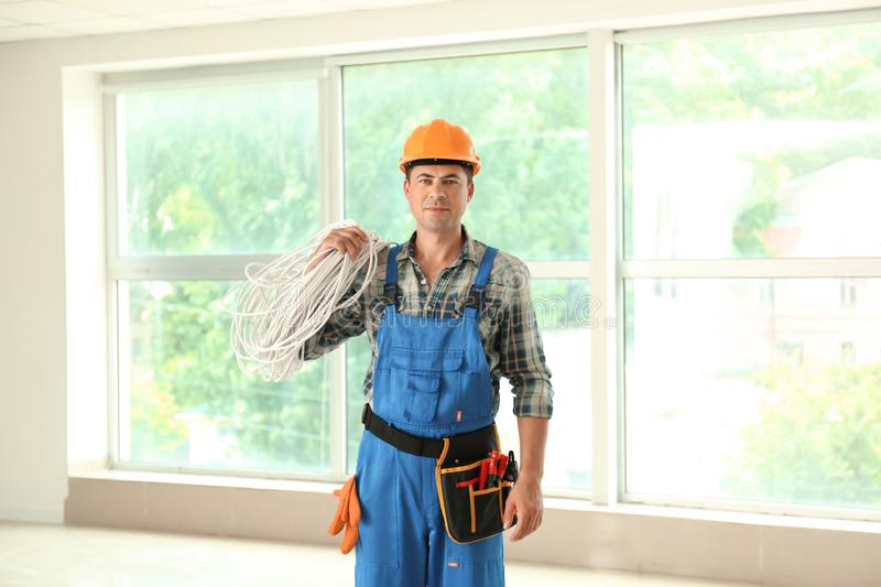Electrician with wires and tools in new empty apartment stock photos