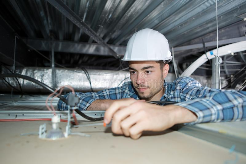 Electrician wiring spotlight from above royalty free stock photography