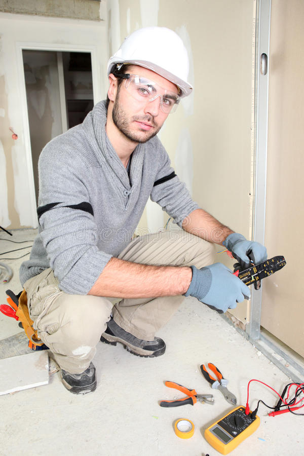 Electrician wiring up a home. Electrician wiring up new home stock image