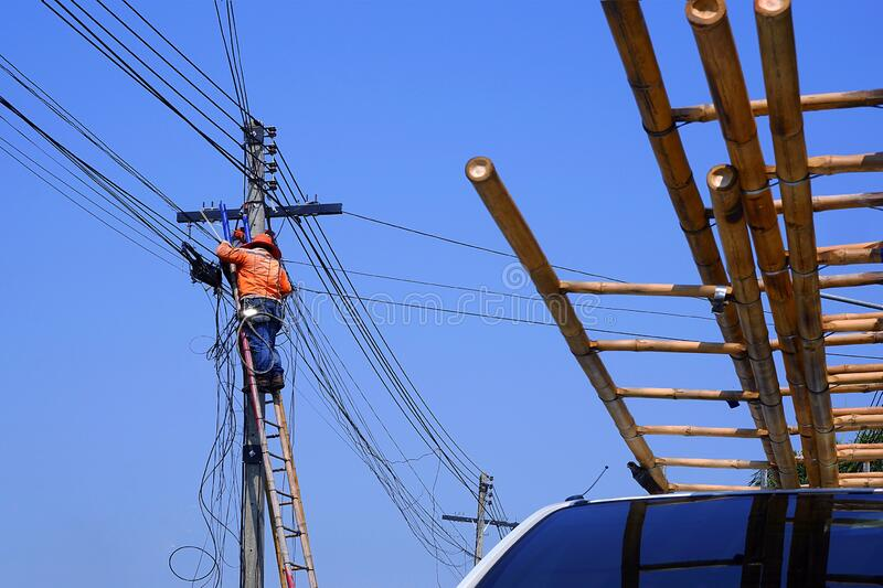 Electrician on wooden ladder are working to install electrical system on electric power pole against blue sky stock images
