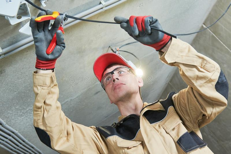 Electrician service. Installer works with cable stock photography