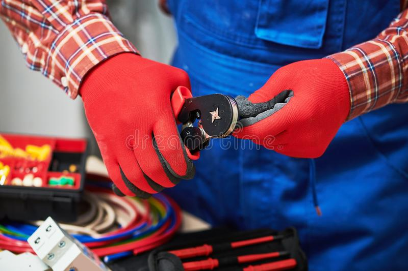 Electrician work with cable. crimping pliers in use royalty free stock image
