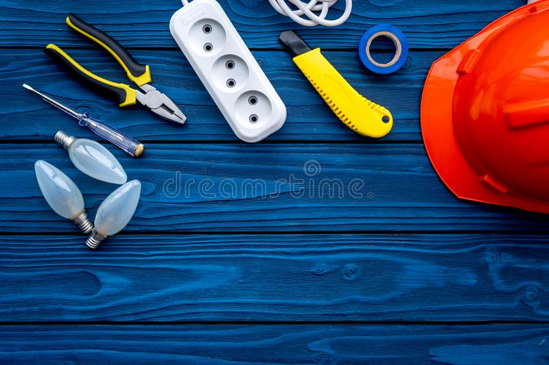 Electrician work concept. Hard hat, tools, bulb, socket outlet on blue wooden background top view copy space stock photography