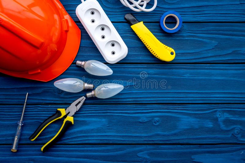 Electrician work concept. Hard hat, tools, bulb, socket outlet on blue wooden background top view copy space royalty free stock photography