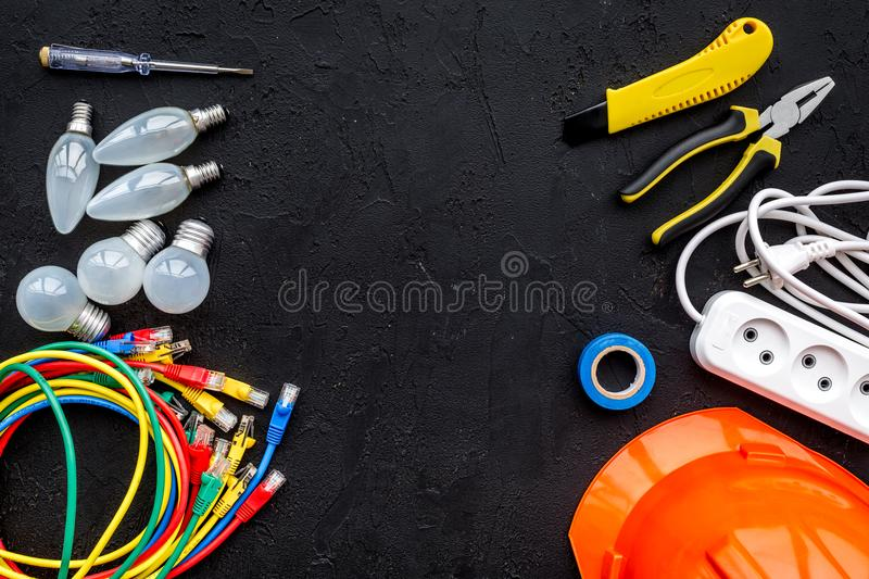 Electrician work concept. Hard hat, tools, cabel, bulb, socket outlet on black background top view space for text stock images