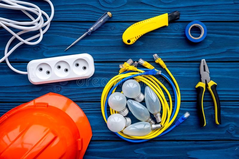 Electrician work concept. Hard hat, tools, cabel, bulb, socket outlet on blue wooden background top view royalty free stock photo