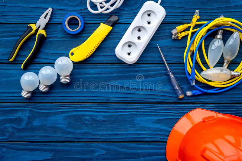 Electrician work concept. Hard hat, tools, cabel, bulb, socket outlet on blue wooden background top view copy space royalty free stock image