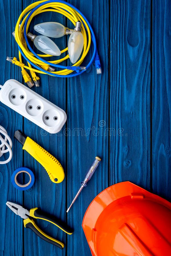 Electrician work concept. Hard hat, tools, cabel, bulb, socket outlet on blue wooden background top view copy space stock photography