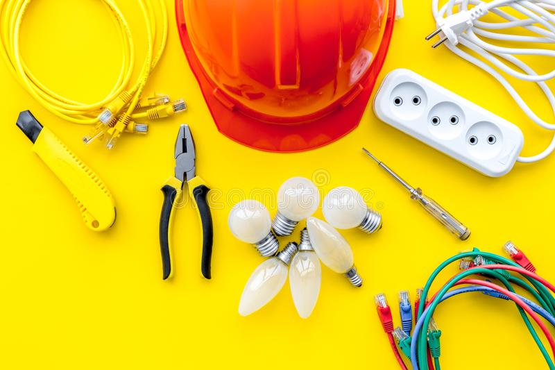 Electrician work concept. Hard hat, tools, cabel, bulb, socket outlet on yellow background top view royalty free stock photography