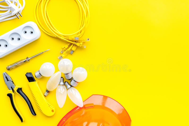 Electrician work concept. Hard hat, tools, cabel, bulb, socket outlet on yellow background top view copy space stock images