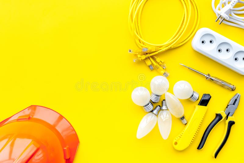 Electrician work concept. Hard hat, tools, cabel, bulb, socket outlet on yellow background top view copy space royalty free stock images