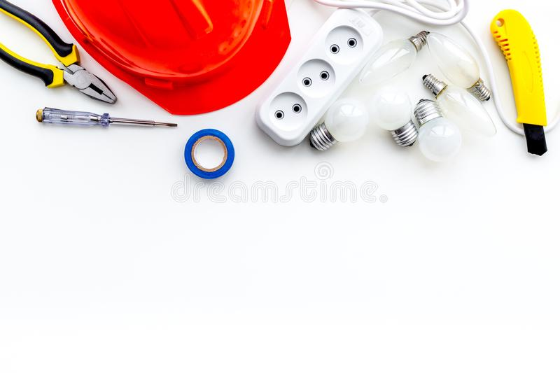 Electrician work concept. Hard hat, tools, cabel, socket outlet on white background top view space for text royalty free stock photos