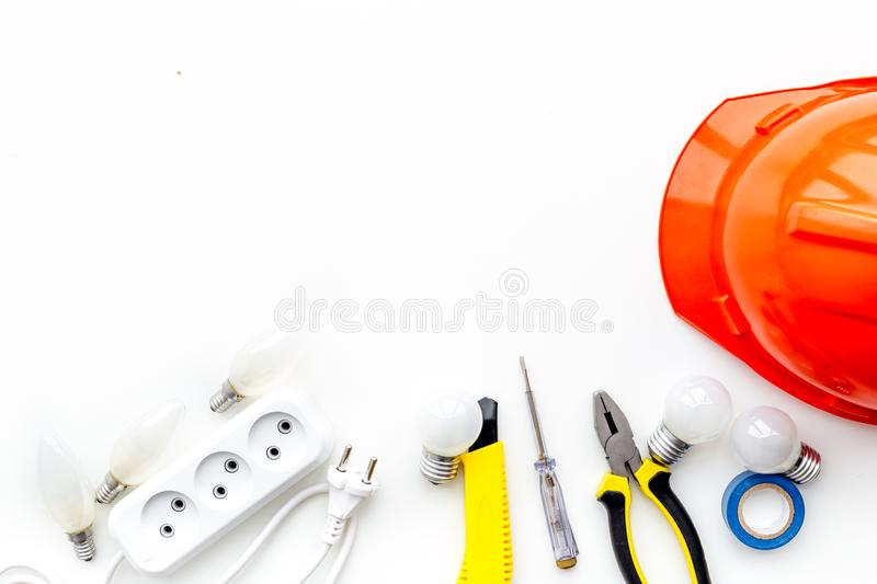 Electrician work concept. Hard hat, tools, socket outlet on white background top view royalty free stock photography