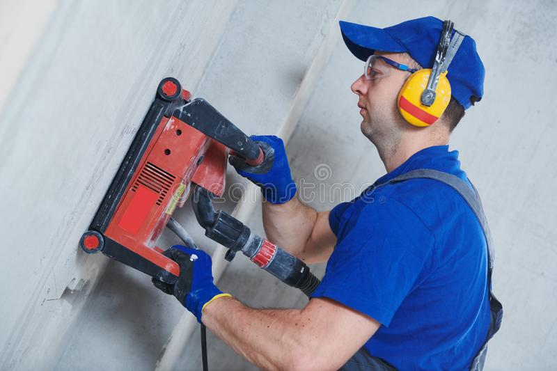 Electrician at work. cutting concrete wall for cabling by diamond slitting machine stock photos
