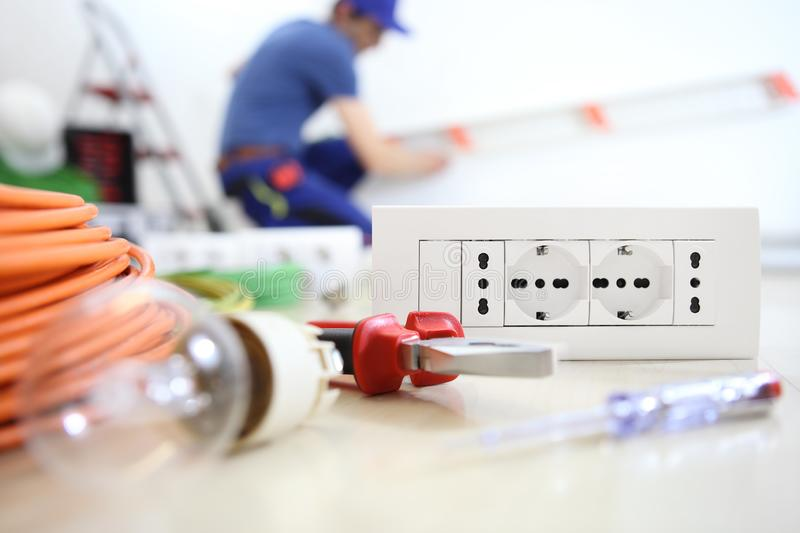 Electrician work with electrical equipment in the foreground, bulb, tools socket, electric circuits, electrical wiring stock images
