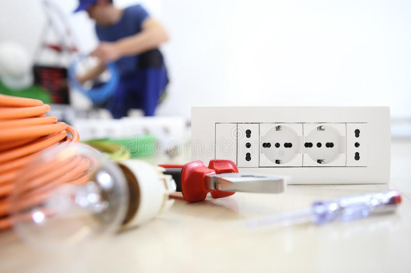 Electrician work with electrical equipment in the foreground, bulb, tools and socket, electric circuits, electrical wiring stock photos
