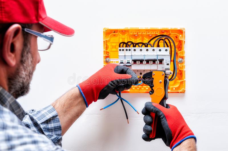 Electrician at work on an electrical panel. stock photos