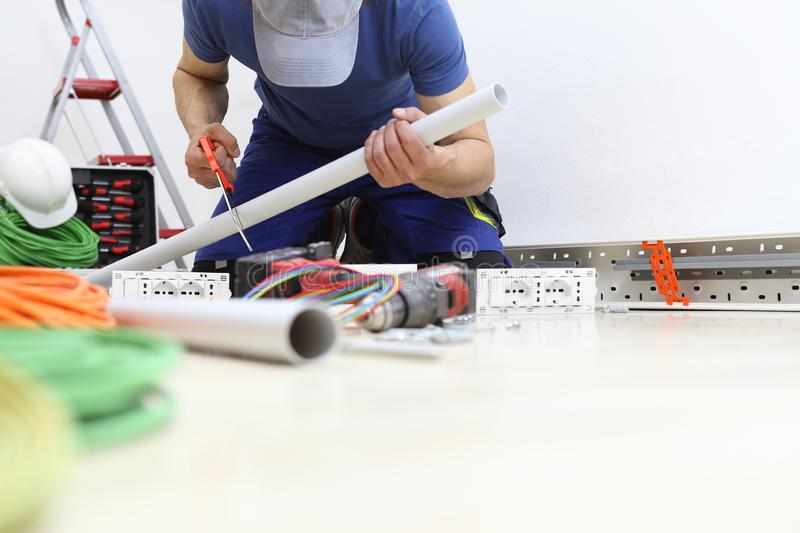 Electrician at work with hacksaw in hand cut the pipe to pass the cables to the socket, install electric circuits, electrical stock photo