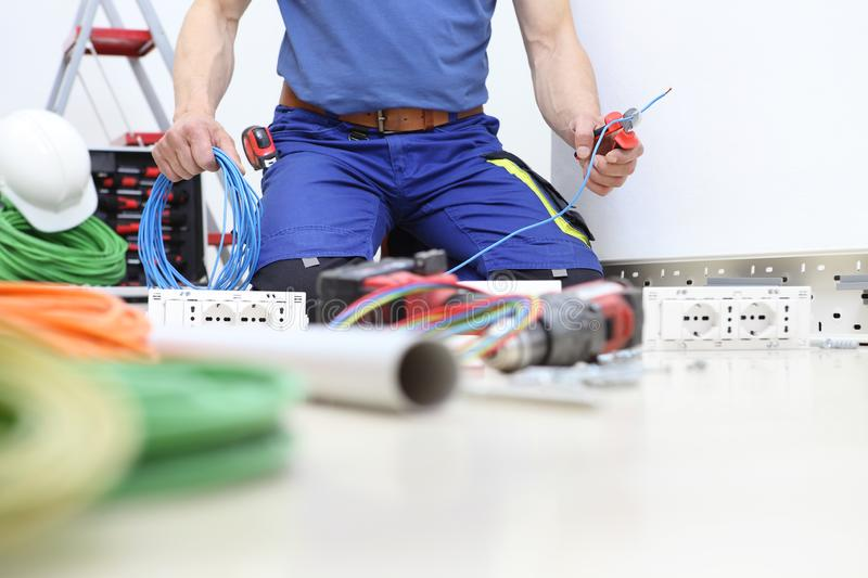 Electrician at work with nippers in hand cut the electric cable, install electric circuits, electrical wiring. stock image