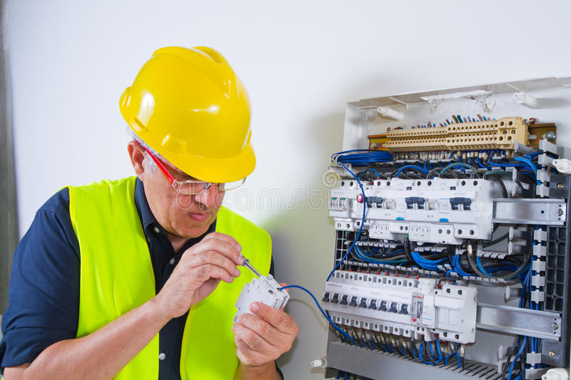 Electrician at work. With an electrician panel royalty free stock photo