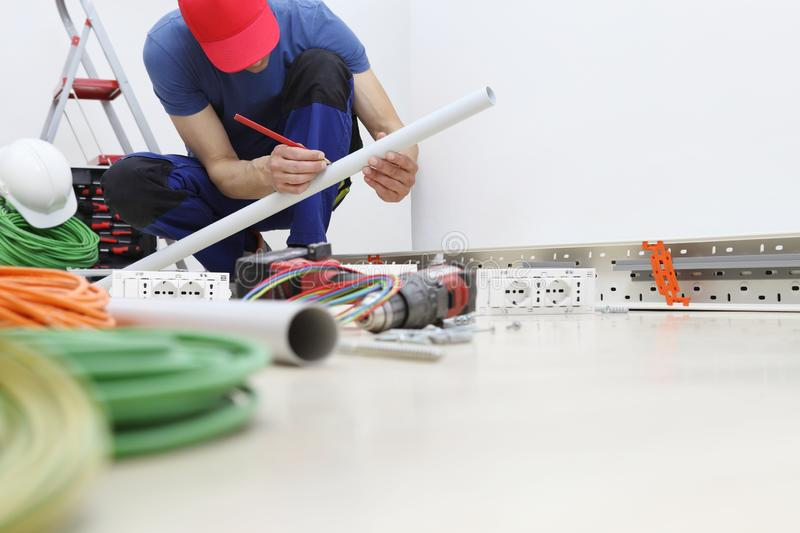 Electrician at work with pencil in hand measures the plastic pipe to pass the electric cables to the sockets, install electric stock image