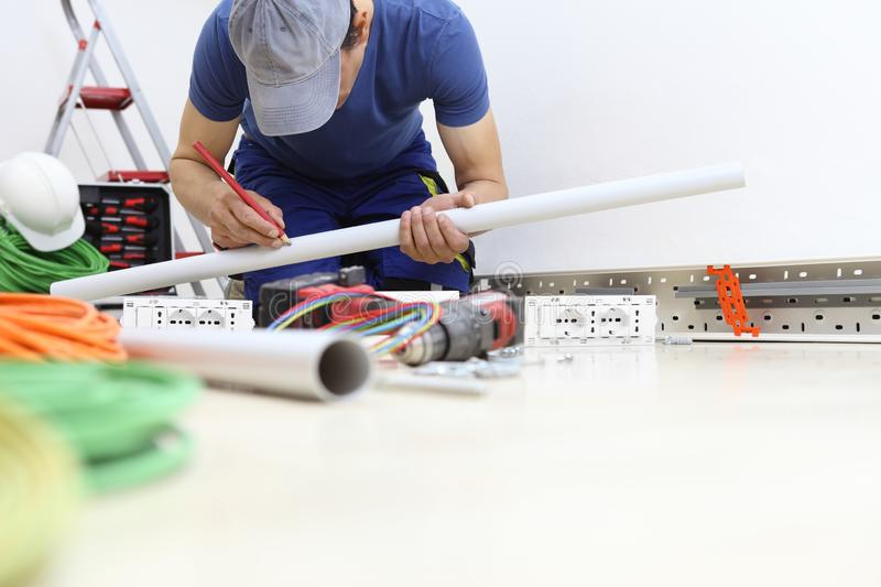 Electrician at work with pencil in hand measures the plastic pipe to pass the electric cables to the sockets, install electric royalty free stock images