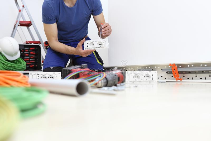 Electrician at work with screwdriver in hand connects the cables to the socket, electric circuits, electrical wiring stock images