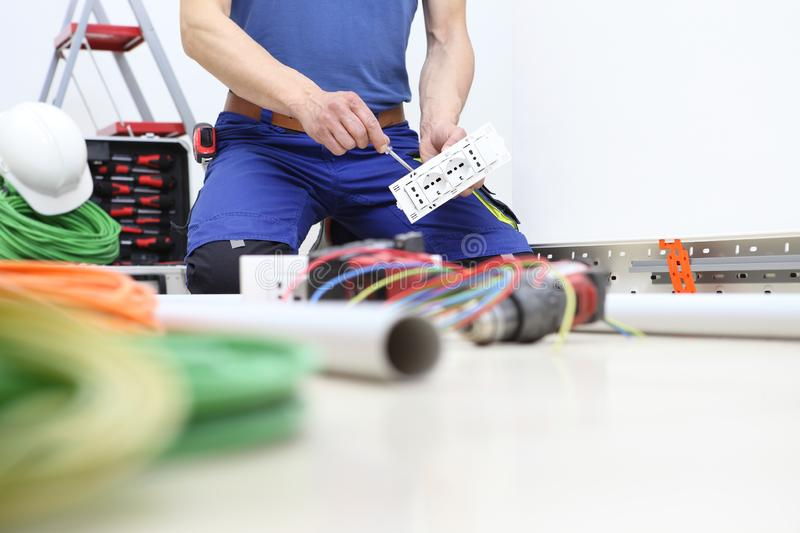 Electrician at work with screwdriver in hand connects the cables to the socket for electrical wiring royalty free stock images