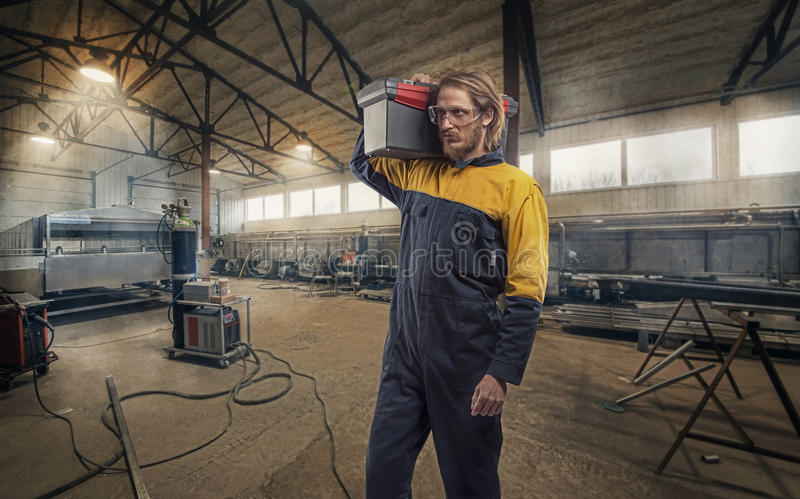 Electrician Worker. Construction worker working at the job. Warehouse background stock image