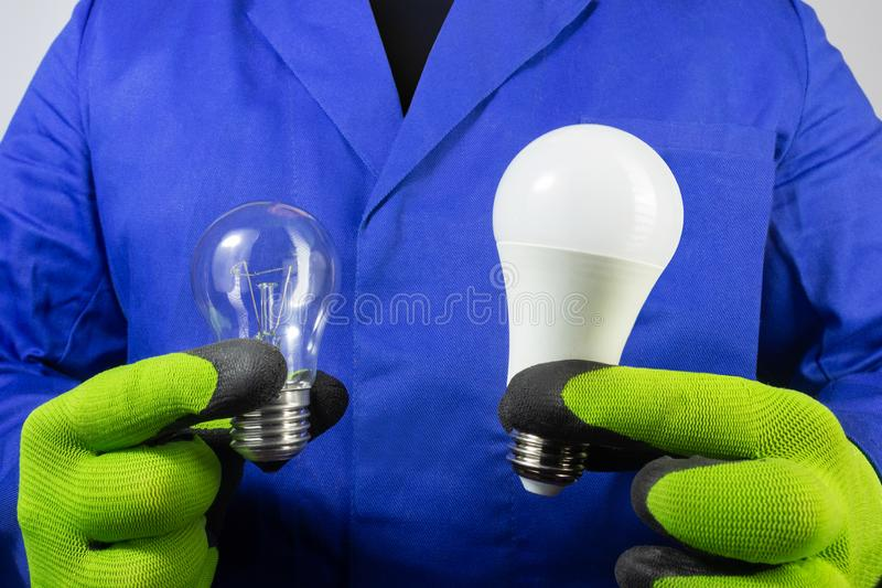 Electrician worker in rober holding types of light bulbs. Photo of electrician in blue robe and gloves holding old bilb and new led light bulb close-up view royalty free stock photography