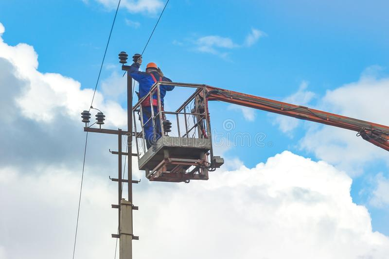 Electrician worker, standing in mobile crane basket and setting up the power line wire royalty free stock photos