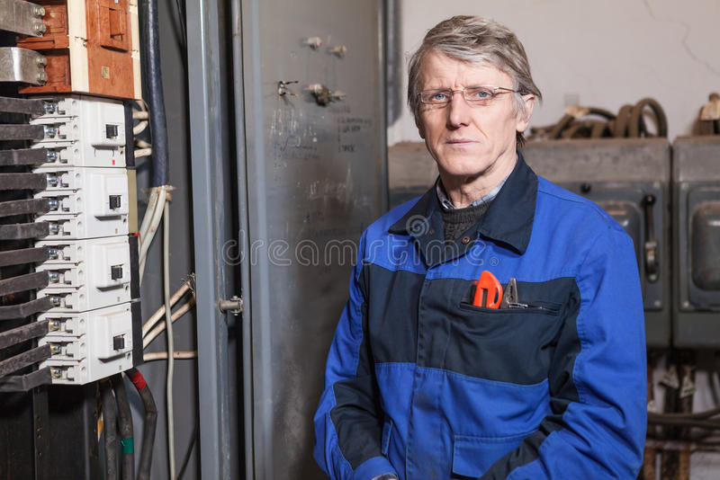 Electrician worker standing near high voltage panel royalty free stock image