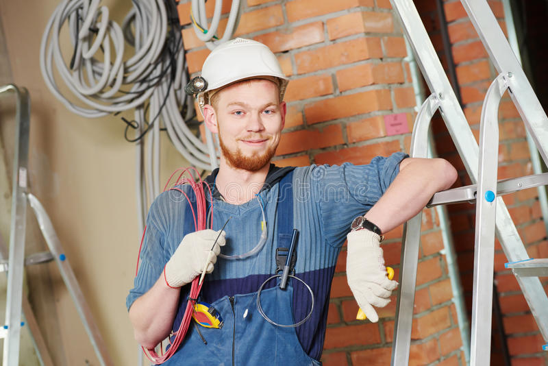 Electrician worker with wiring. Electrician builder engineer worker with cable wiring at indoor construction site royalty free stock photography