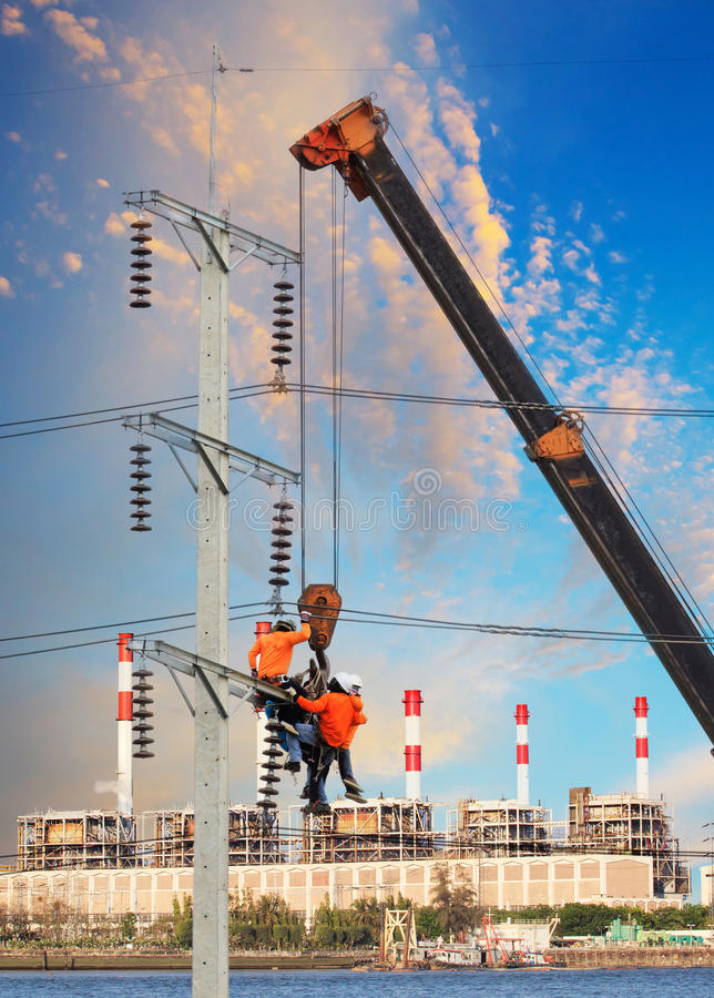 Electrician worker working on high voltage electric pole with cr. Ane against factory building background stock photos