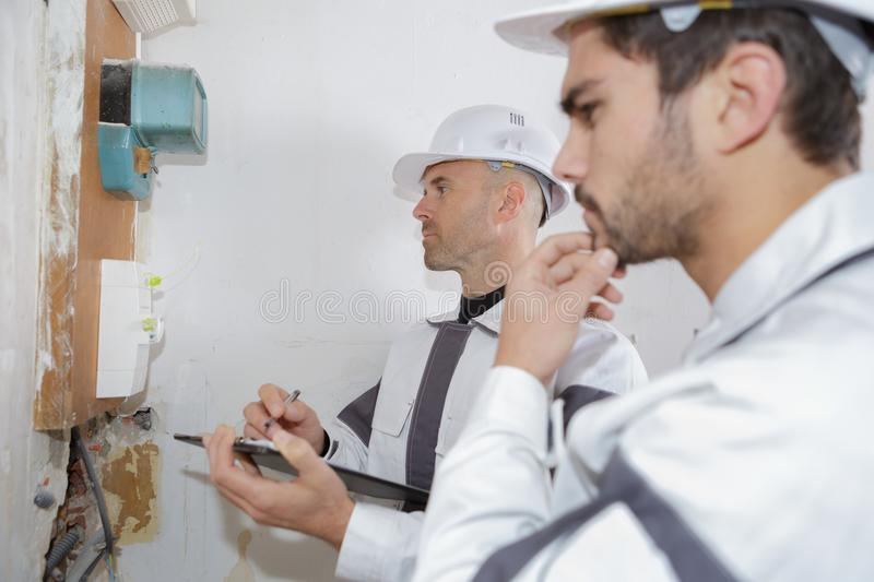 Electrician workers checking voltage fuse board royalty free stock photo