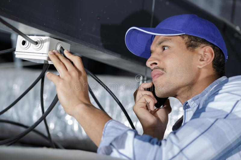 Electrician working on cable on ceiling indoors royalty free stock photography