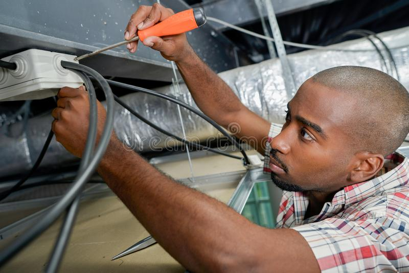 Electrician working on ceiling wiring stock images