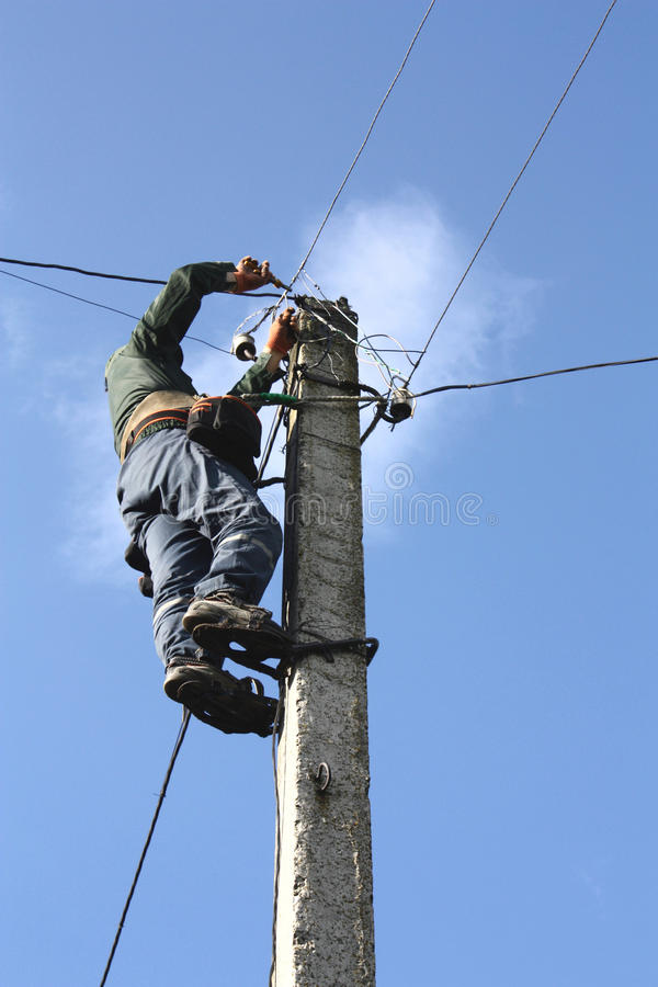 Electrician working on electric power pole. Against the blue sky stock images