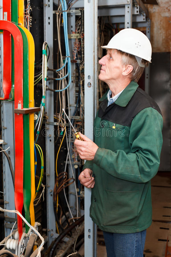 Electrician working in hard hat with cables stock image